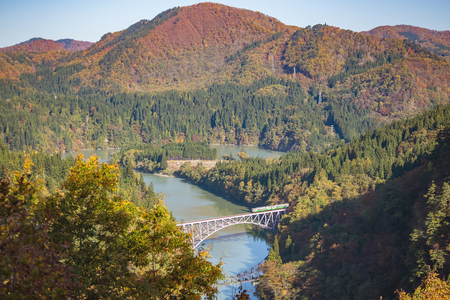 first tadami river iron bridge with green train in autumn scenery, Fukushima, Japan Banco de Imagens