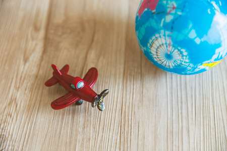 red toy plane and globe model on wood background Standard-Bild