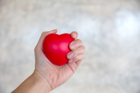 womans hand squeezing red rubber heart, health concept, love problem