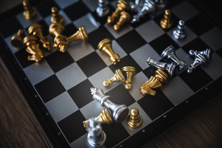 Gold and silver chessmen on checkerboard, concept for business competition