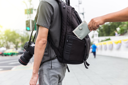 closeup pickpockets hand stealing purse from backpacker