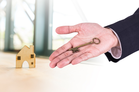 man holding key with home shape wood model on background, real estate concept