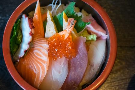 closeup mixed sashimi on rice in black bowl, japanese food