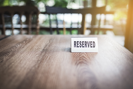 steel reserved sign on wood table in restaurant