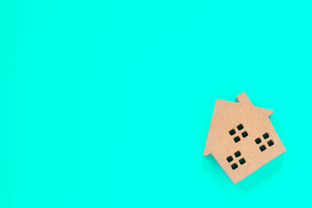 home shape wood model on blue background, concepts for real estate and business