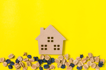 home model with dried flowers on yellow background