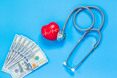 red rubber heart and stethoscope on blue background with dollar banknotes, health concept