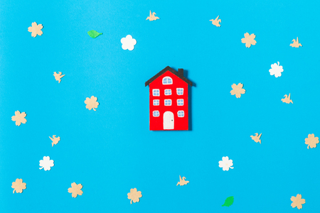 colorful home model on blue background decorated with paper flowers