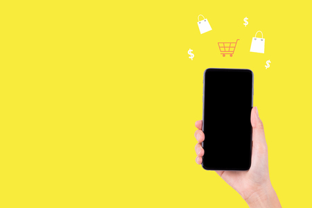 hand with smart phone for shopping service on yellow background, online marketing concept