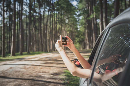 woman tourist taking photo by smartphone in car while traveling in pine forest