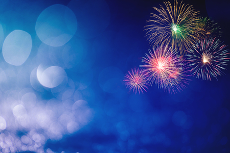 colorful fireworks at right corner with blue bokeh background