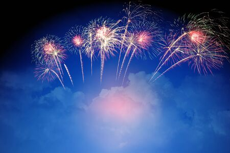 colorful fireworks on cloudy blue sky background