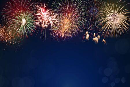 Fuegos artificiales de colores sobre fondo azul oscuro bokeh, concepto de celebración