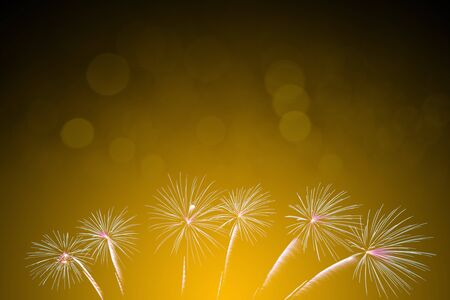 colorful fireworks on yellow bokeh background, celebration concept 写真素材