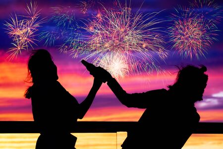 shadow of women celebrate with colorful fireworks display on sunset sky, celebration concept