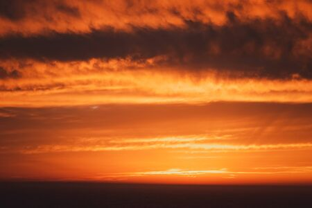 golden sunset sky with layer of cloud