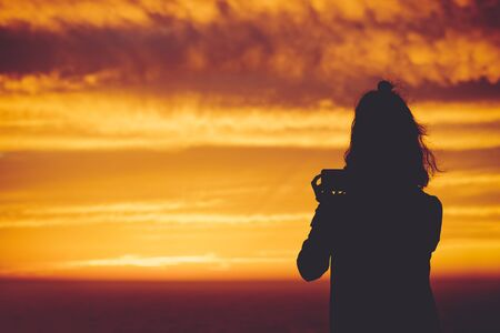 silhouette woman taking photo with mobile phone of golden sunset sky, travel concept