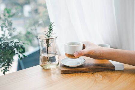 woman's hand holding cup of coffee with white curtain and green garden outside