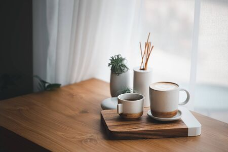cup of hot coffee and tea on wood table besides window Stock Photo