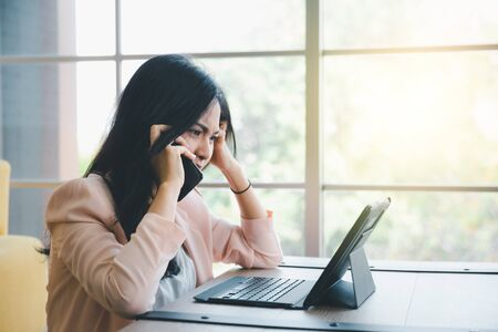 beautiful working woman using smart phone with tablet on desk with moody emotional Foto de archivo