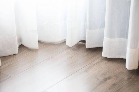 bottom of transparent curtain on wooden floor
