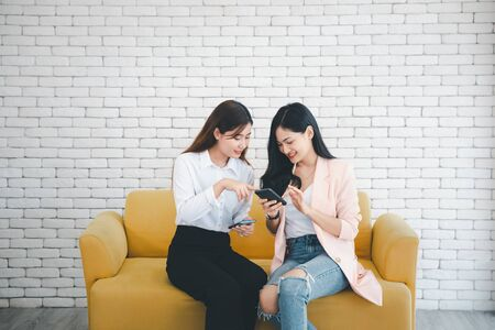 beautiful women sitting on yellow sofa and chatting about something in their smart phone