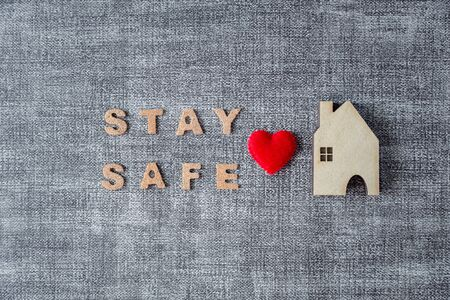 stay safe word with home model and heart on grey background, coronavirus prevention concept