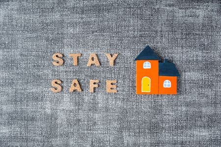 stay safe word with orange color home model on grey background, coronavirus prevention concept