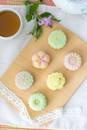 colorful pastel snow skin mooncakes with hot tea, chinese mid autumn festival food