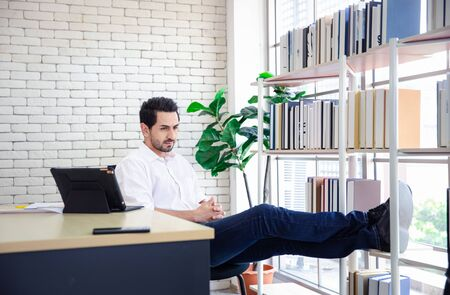 businessman sitting with legs on book shelf thinking something in workplace 写真素材