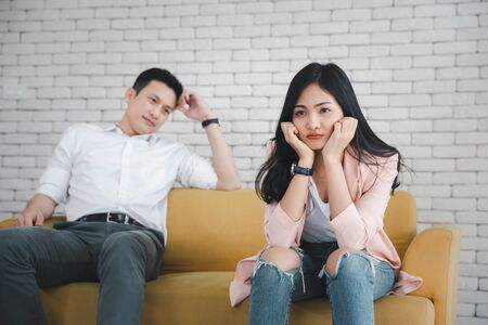 young couple sitting on sofa having conflict, focus on woman 写真素材