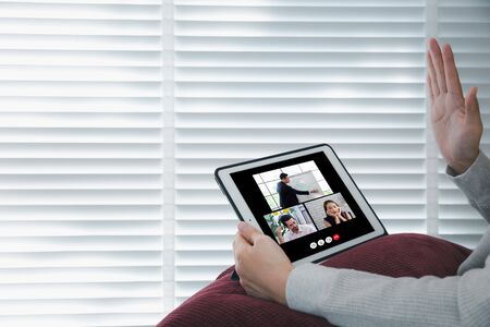 woman raised hand with video confernce screen on tablet while working from home during covid-19, online meeting concept Фото со стока