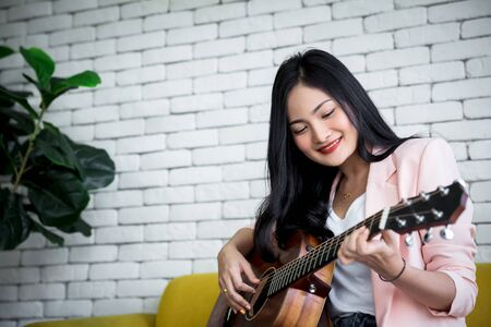 smart casual dress woman playing guitar in living room with smiling face Фото со стока