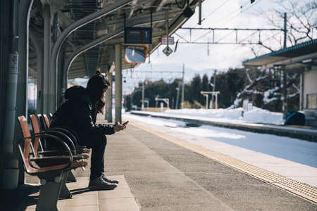 lonely woman looking at smartphone waiting for train at station, travel concept