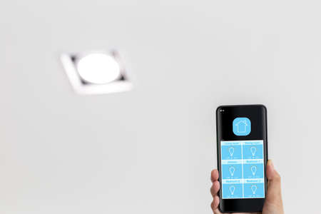 woman hand holding mobile phone showing smart home app screen on lighting control page 免版税图像