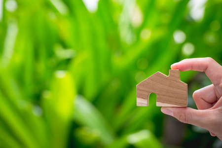 woman's hand holding wooden home model on her fingers with green nature background on sunny day