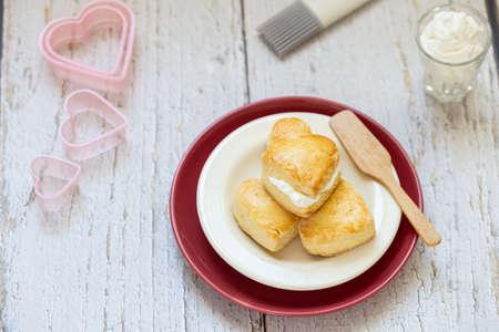 homemade plain scones arranged on dish with fresh cream for tea break