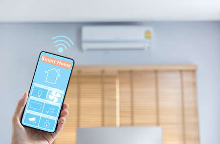 woman hand holding mobile phone showing smart home app screen with air condition on background