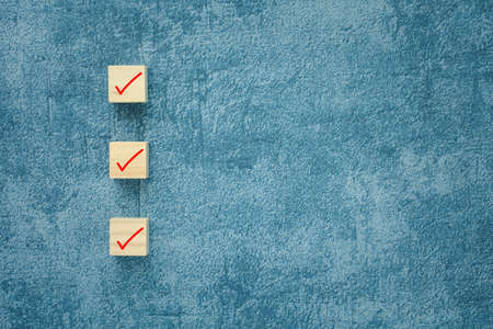 check mark on wooden cubes with blue background, checklist concept with copy space