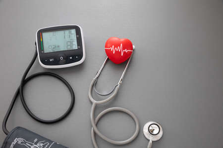 red rubber heart and stethoscope with blood pressure measurement machine on dark grey background, health concept Фото со стока
