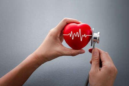 hands holding stethoscope checking on red rubber heart with cardiogram on dark grey background, health concept Фото со стока