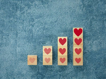 heart on wooden cubes arranged in bar graph shape on blue background, health concept