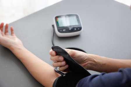 self blood pressure and heart rate measurement with blood pressure monitor machine, healthcare and medical concept