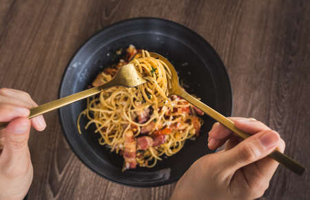 shot of person's hand having spicy bacon pasta on table 免版税图像