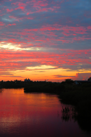 On a quiet morning, by the river, beautiful sunrises and strong colors of the sky reflect on the river, forming a charming color.