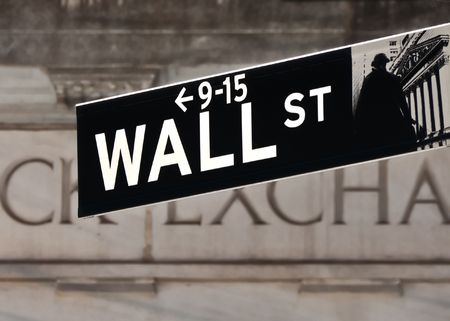 Wall street sign in front of Stock Exchange building in New York photo