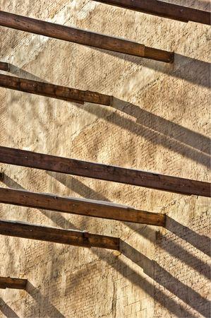 Wooden beams in between brick building with shadows Фото со стока