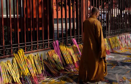 sotana: Un monje en un templo caminando pasa el incienso por oraciones Foto de archivo