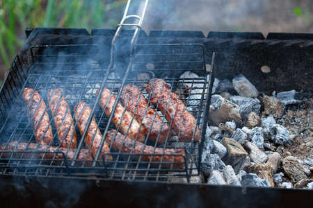 Meat sausages on barbecue grill cooked for summer family dinner. Close up view