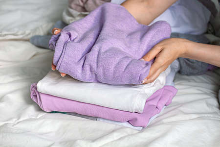 Feminine hands sorting clothes before laundry. Keeping clean and fresh in the house